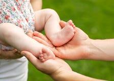 Babyfüße gehöhlt in Vaterhände Stockfotografie