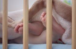 Babyfüße im Bett Stockfotografie
