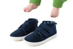 Babyfüße mit den zu großen blauen Kinderschuhen lokalisiert auf Weiß Lizenzfreie Stockfotografie