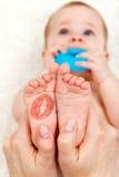 Babyfüße mit Lippenstiftkusskennzeichen Stockbild