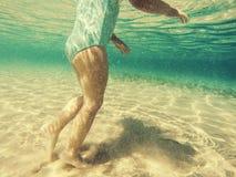 Babyfüße unter Wasser gehend Lizenzfreies Stockfoto