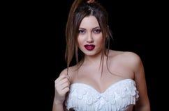 Babyface female model wearing strapless white dress on black background Stock Images