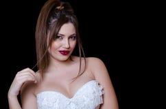 Babyface female model wearing strapless white dress on black background Royalty Free Stock Photography