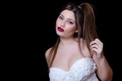 Babyface kvinnlig modell som bär den axelbandslösa vita klänningen på svart bakgrund royaltyfri fotografi