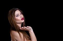Babyface kvinnlig modell som bär den axelbandslösa vita klänningen på svart bakgrund royaltyfri bild