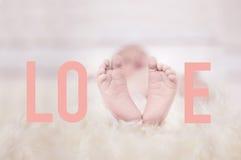 Babyfeet auf dem Pelz, der die Wortliebe bildet Lizenzfreie Stockbilder