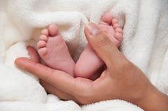 Babyfeet con la mano de la mam3a Imagen de archivo