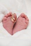 Babyfeet con los anillos de bodas Foto de archivo libre de regalías