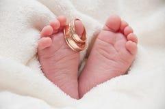 Babyfeet con los anillos de bodas Imagen de archivo libre de regalías