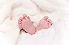 Babyfeet con los anillos de bodas Fotos de archivo