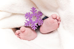 Babyfeet with snowflake Stock Photos