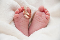 Babyfeet with wedding rings Royalty Free Stock Image