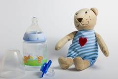 Babyflaschen, Friedensstifter und Spielwaren, die auf einem weißen Hintergrund liegen lizenzfreie stockfotografie