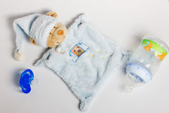 Babyflaschen, Friedensstifter und Spielwaren, die auf einem weißen Hintergrund liegen stockbilder
