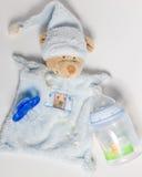 Babyflaschen, Friedensstifter und Spielwaren, die auf einem weißen Hintergrund liegen lizenzfreie stockbilder