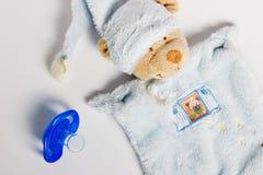 Babyflaschen, Friedensstifter und Spielwaren, die auf einem weißen Hintergrund liegen stockbild