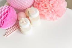 Babyflaschen mit Muttermilch mit verschiedenem festlichem Papierdekor Es ` s ein Mädchen- oder Babygeburtstagsfeierkonzept lizenzfreie stockfotos