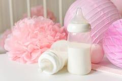Babyflaschen mit Muttermilch mit verschiedenem festlichem Papierdekor und Ballonen vor Babyschlafzimmer Es ` s ein Mädchen oder B lizenzfreie stockfotografie