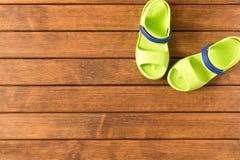 BabyFlipflops auf hölzernem Hintergrund Kind-` s Schuhe Der Betrug lizenzfreie stockfotografie