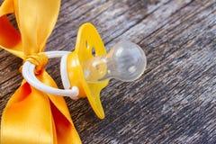 Babyfriedensstifter auf Holztisch Lizenzfreie Stockfotografie