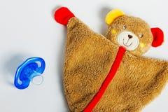 Babyfriedensstifter und -spielwaren, die auf einem weißen Hintergrund liegen stockfoto