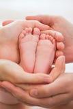 Babyfuß in den Händen von Eltern Stockfotos