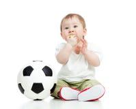 Babyfußballspieler mit Kugel und Pfeife Stockfoto