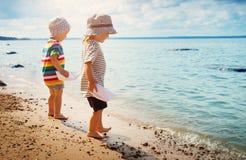 Babygirl和babyboy开会在海滩 免版税库存照片