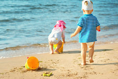 Babygirl и babyboy играть на пляже стоковая фотография rf