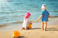 Babygirl и babyboy играть на пляже стоковая фотография