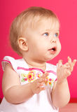 Babygirl. Beautiful babygirl claping one's hands on pink backround Royalty Free Stock Photos