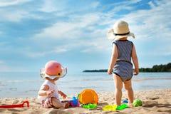 Babygirl and babyboy on the beach Stock Photos