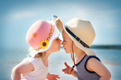 Babygirl and babyboy kissing on the beach royalty free stock images