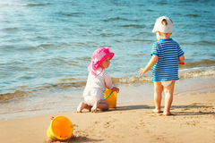 Babygirl and babyboy playing on the beach. In summer Stock Photography