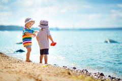 Babygirl and babyboy sitting on the beach. Babygirl and babyboy standing on the beach in summer hats and holding paper ships Stock Photos