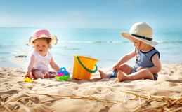 Babygirl and babyboy sitting on the beach. In straw hats Royalty Free Stock Photo