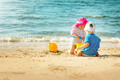 Babygirl and babyboy sitting on the beach Royalty Free Stock Image