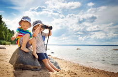 Babygirl and babyboy sitting on the beach. In summer hats Royalty Free Stock Image