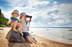 Babygirl and babyboy sitting on the beach Royalty Free Stock Image