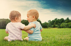 Babygirl and babyboy sitting in the grass. On sunny day Stock Photography