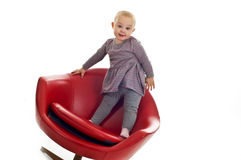 Babygirl on a chair. Babygirl on red skin armchair Stock Images