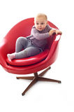 Babygirl on a chair. Babygirl on red skin armchair Royalty Free Stock Images
