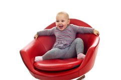 Babygirl on a chair. Babygirl on red skin armchair Stock Photo
