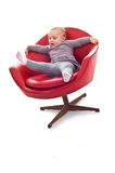 Babygirl on a chair. Babygirl on red skin armchair Stock Photography