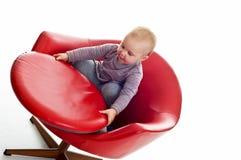 Babygirl on a chair. Babygirl on red skin armchair Stock Photos