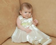 Babygirl in holiday clothes. Babygirl on a sofa in holiday clothes Stock Image