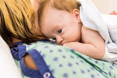 Babygirl Lying On Mother In Hospital. Closeup of adorable newborn babygirl lying on mother in hospital Stock Image