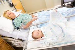 Babygirl se situant dans le berceau avec la femme sur l'hôpital Image stock