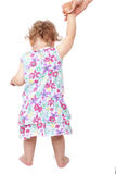 Babygirl walking. Babygirl in summer dress holding mothers hand and walking on white background, back view. Learning to walk Royalty Free Stock Images