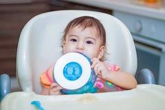 Babyglimlach die in de keuken op het sittting op de lijst eten Stock Foto
